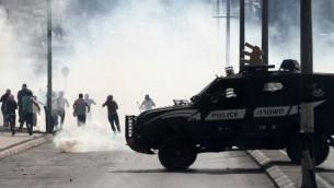 مركبة عسكرية إسرائيلية تسير أمام محتجين فلسطينيين خلال مواجهات في 13 أكتوبر، 2015 في مدينة بيت لحم بالضفة الغربية. (AFP/MUSA AL-SHAER)