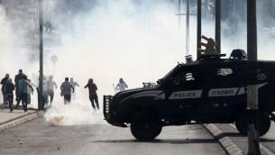مركبة شرطة اسرائيلية امام متظاهرين فارين خلال اشتباكات في بيت لحم في الضفة الغربية، 13 اكتوبر 2015 (AFP/ MUSA AL-SHAER)