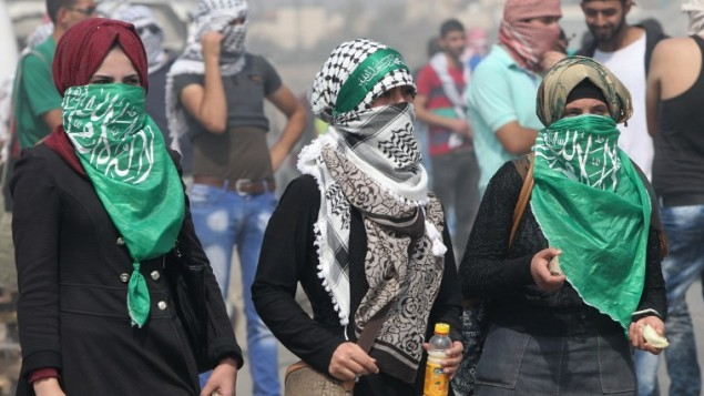 """طالبات فلسطينيات من جامعة """"بوليتكنك فلسطين"""" تقمن بإلقاء الحجارة باتجاه مستوطنة """"بيت حاغاي"""" الإسرائيلية، عند المدخل الجنوبي لمدينة الخليل بالضفة الغربية، 18 أكتوبر، 2015. (AFP Photo/Hazem Bader)"""