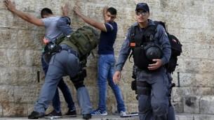 عناصر من الشرطة الإسرائيلية تقوم بتفتيش شبان فلسطينيين عند باب العامود في البلدة القديمة بمدينة القدس، 18 أكتوبر، 2015.(AFP/Ahmad Gharabli)