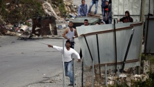 متظاهرون فلسطينيون يرشقون الحجارة باتجاه جنود اسرائيليين في مدخل بلدة بيت عنون بالقرب من الخليل، 26 اكتوبر 2015 (AFP/ THOMAS COEX)