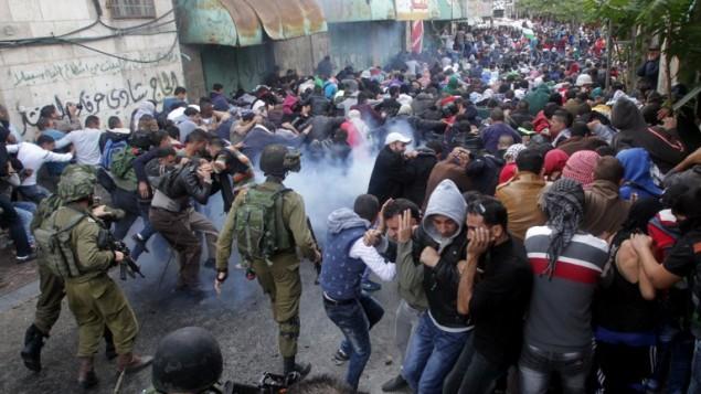 القوات الإسرائيلية تطلق الغاز المسيل للدموع لتفريق المتظاهرين الفلسطينيين خلال تظاهرة في مدينة الخليل بالضفة الغربية، 27 أكتوبر، 2015. (AFP PHOTO / HAZEM BADER)