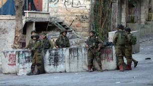 جنود اسرائيليون يحرسون بالقرب من مكان وقوع محاولة طعن جندي قبل اطلاق النار على المعتدي الفلسطيني وقتله في مدينة الخليل، 28 اكتوبر 2015 (AFP Photo/Hazem Bader)