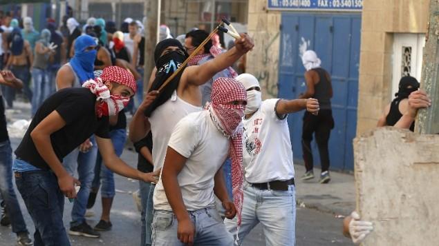 فلسطينيون يرشقون الحجارة باتجاه عناصر الأمن الإسرائيلية في حي شعفاط في القدس الشرقية، 5 اكتوبر 2015 (AHMAD GHARABLI / AFP)