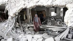 امرأة فلسطينية تسير وسط أنقاض منزل بعد أن قامت االقوات الإسرائيلية بهدم منزلين فلسطينيين قاما بتنفيذ هجمات، في حي جبل المكبر في القدس الشرقية، 6 أكتوبر، 2015. (AFP/THOMAS COEX)