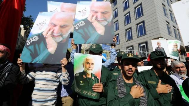 رجال ايرانيون يرفعون صورة الجنرال حسين همداني الذي قتل اثناء القتال في سوريا، 11 اكتوبر 2015 (ATTA KENARE / AFP)