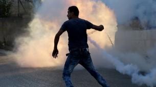 متظاهر فلسطيني يستخدم مقلاعا خلال مواجهات مع القوات الإسرائيلية في 31 يوليو، 2015 بالقرب من مخيم الجلزون للاجئين ومستوطنة بين إيل، شمال رام الله بالضفة الغربية. (AFP/ ABBAS MOMANI)