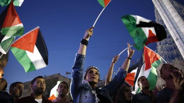 فلسطينيون يلوحون بالعلم الفلسطيني في رام الله بينما يشاهدون بثا مباشرا لرفع العلم الفلسطيني امام مقر الأمم المتحدة في نيويورك، 30 سبتمبر2015 (ABBAS MOMANI / AFP)