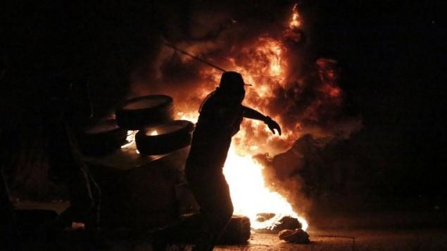 شبان فلسطينيون يحرقون الاطارات المطاطية خلال مواجهات مع جنود اسرائيليين بالقرب من مستوطنة بيت ايل في الضفة الغربية، 4 اكتوبر 2015 (Abbas Momani/AFP)