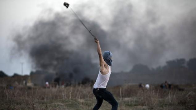 متظاهر فلسطيني يستخدم  مقلاعا لإلقاء حجارة تجاه الجنود الإسرائيليين خلال مواجهات بالقرب من السياج الحدودي بين إسرائيل ووسط قطاع غزة، 15 أكتوبر، 2015. (Mohammed Abed/AFP)