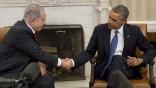 الرئيس الأمريكي باراك أوباما (من اليمين) يصافح رئيس الوزراء الإسرائيلي بينيامين نتنياهو في المكتب البيضاوي في البيت الأبيض بالعاصمة واشنطن، 3 مارس، 2014. (AFP/Saul Loeb)