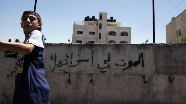 طفل فلسطيني يمر امام جدار عليه الشعار 'الموت لإسرائيل' في حي بيت حنينا في القدس الشرقية، يوليو 2008 (Michal Fattal/Flash90)