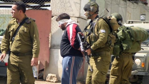 صورة توضيحية لجنود إسرائيليين يعتقلون فلسطينيين. (Najeh Hashlamoun/Flash90)