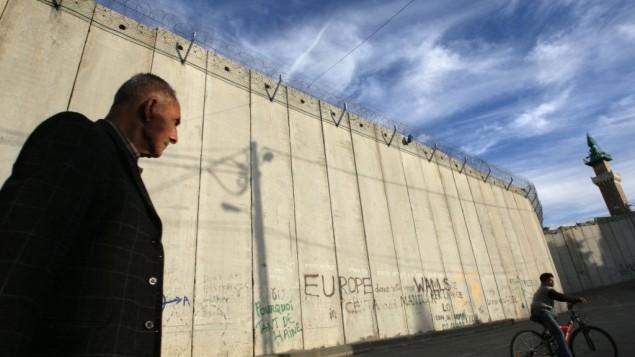 رجل فلسطيني يمر بجانب الجدار الفاصل الإسرائيلي في قرية أبو ديس في الدقس الشرقية. (Kobi Gideon/Flash90)