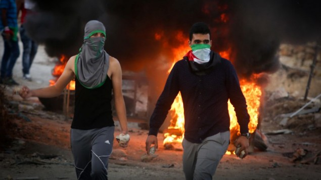 فلسطينيون يرشقون الحجارة خلال مواجهات مع قوات الامن الإسرائيلية بالقرب من حاجز حزمة في الضفة الغربية، 30 سبتمبر 2015 (Flash90)