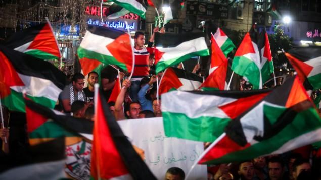 فلسطينيون يلوحون بالعلم الفلسطيني في رام الله بينما يشاهدون بثا مباشرا لرفع العلم الفلسطيني امام مقر الأمم المتحدة في نيويورك، 30 سبتمبر2015 (FLASH90)