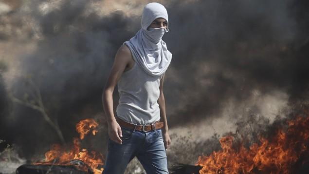 متظاهر فلسطيني خلال تظاهرة في مدينة رام الله بالضفة الغربية، الإثنين، 5 أكتوبر، 2015. (Photo by Flash90)