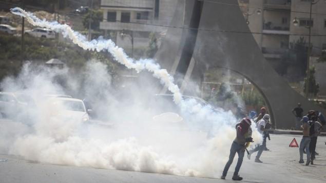 محتجون فلسطينيون يفرون من الغاز المسيل للدموع خلال مواجهات مع الشرطة بعد تظاهرة في مدينة رام الله بالضفة الغربية، 5 أكتوبر، 2015. (Photo by Flash90)