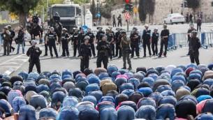 مصلون مسلمون وقوات الشرطة الإسرائيلية في حي وادي الجوز في القدس الشرقية، 9 أكتوبر، 2015. الشرطة الإسرائيلية أعلنت عن وضع قيود على سن الفلسطينيين الراغبين بدخول البلدة القديمة، وسمحت للجرال فوق سن ال45 فقط وجميع النساء بدخولها. (Yonatan Sindel/Flash90)