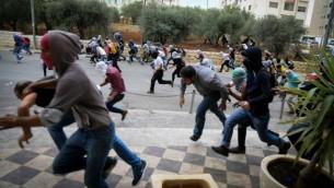 محتجون فلسطيينون يلقون الحجارة باتجاه القوات الإسرائيلية (لا تظهر بالصورة) خلال إحتجاجات بالقرب من مستوطنة بيت إيل، بالقرب من مدينة رام الله في الضفة الغربية، 10 أكتوبر، 2015. (Flash90)