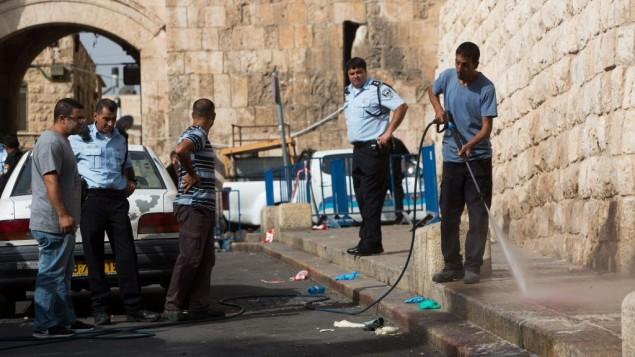 رجل يقوم بتنظيف الموقع الذي شهد محاولة هجوم طعن شرطي عند باب الأسباط في البلدة القديمة بمدينة القدس، 12 أكتوبر، 2015. (Yonatan Sindel/Flash90)