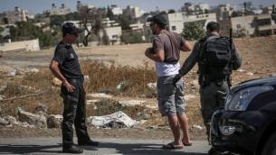 عناصر من شرطة حرس الحدود يفتشون سائقا فلسطينيا عند خروجه من حي جبل المكبر في القدس الشرقية، 14 أكتوبر، 2015. (Hadas Parush/Flash90)