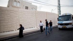 فلسطينيون يمشون امام جدار اسمنتي يفصل بين حي جبل المكبر العربي وحي ارمون هناتسيف اليهودي بمعظمه، 18 اكتوبر 2015 (Yonatan Sindel/Flash90)