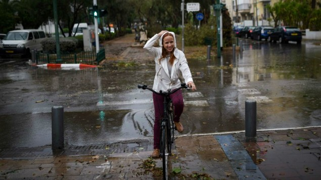 النائبة ستاف شافير (المعسكر الصهيوني) على متن دراجتها تحت الأمطار الغزيرة اثناء عاصفة في تل ابيب، 25 اكتوبر 2015 (Ben Kelmer/Flash90)
