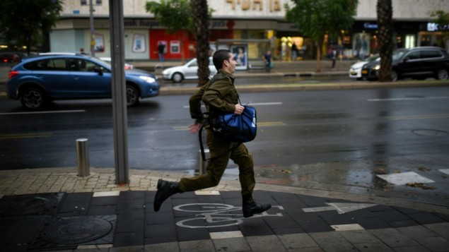 جندي اسرائيلي يحاول الفرار من الامطار خلال عاصفة في تل ابيب، 25 اكتوبر 2015 (Ben Kelmer/Flash90)