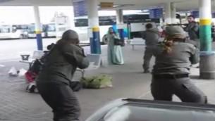 صورة شاشة لتصوير التقط بواسطة هاتف ذكي يظهر قوات الامن تحيط امرأة عربية من اسرائيل تحمل سكين بعد ان ورد انها حاولت طعن حارس في محطة الحافلات المركزية في العفولة، 9 اكتوبر 2015 (screen capture)