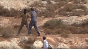صورة شاشة من فيديو يظهر ناشط يميني متطرف ملثم يهاجم مدير جمعية 'حاخامات لحقوق الإنسان' وهو يحمل سكين (YouTube)