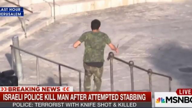 شاب يجري مسرعا بإتجاه رجل شرطة وهو يحمل سكينا في القدس، 14 أكتوبر، 2015، كما يظهر في صورة التقطتها عدسة كاميرا  طاقم إخباري من شبكة MSNBC. (لقطة شاشة: MSNBC)
