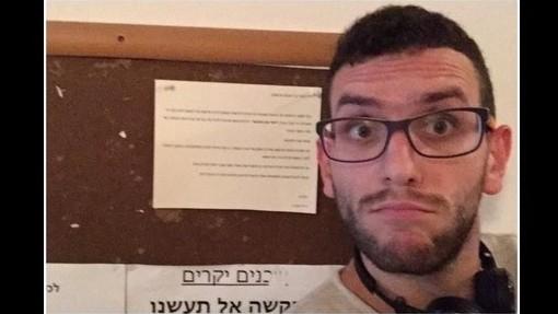 زيزو أبو الهوى، من سكان تل أبيب العرب، يلتقط صورة 'سلفي' أمام إعلان معاد للعرب تم تعليقه في البناية التي يسكن فيها. 12 أكتوبر، 2014. (لقطة شاشة: Facebook)
