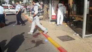 محققون من الشرطة في موقع هجوم الطعن في رعنانا، 13 أكتوبر، 2015. (لقطة شاشة: الشرطة الإسرائيلية)