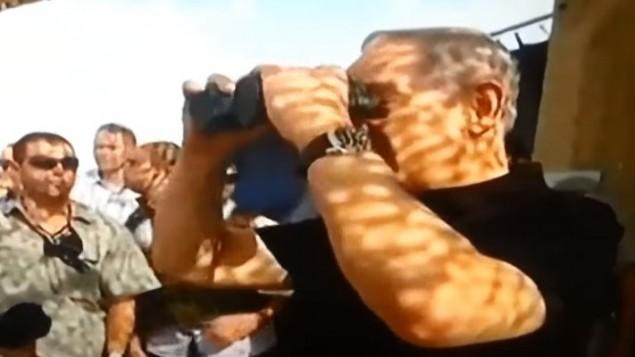 رئيس الوزراء بنيامين نتنياهو ينظر خلال ناضور عدساته مغطاة على حدود قطاع غزة، 20 اكتوبر 2015 (YouTube screenshot)