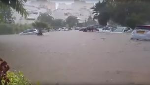 سيارات مغمورة بالمياه خلال فيضان في مدينة عسقلان، 8 نوفمبر 2015 (screen capture: YouTube)