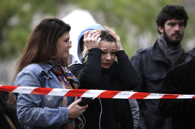 """سيدة تفاعل مع مشهد الزهور والرسائل التي وُضعت في مكان قريب من مسرح باتاكلان في الدائرة ال11 لمدينة باريس في 14 نوفمبر، 2015، بعد يوم من سلسلة من الهجمات ضربت العاصمة الفرنسية وأسفرت عن مثتل أكثر من 128 شخصا.  في مسرح باتالكان قُتل حوالي 80 شخصا بعد إطلاق النار عليهم في باريس في 13 نوفمبر، خلال حفل للفرقة الأمريكية """"ايجلز اوف ديث ميتال"""". (AFP PHOTO / KENZO TRIBOUILLARD)"""
