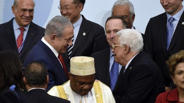رئيس الوزراء بينيامين نتنياهو يتحدث مع رئيس السلطة الفلسطينية محمود عباس خلال مؤتمر الأمم المتحدة للتغير المناخي، في لوبورجيه، خارج باريس، 30 نوفمبر، 2015. (AFP/POOL/MARTIN BUREAU)