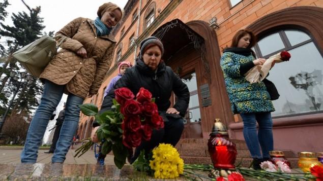 افراد يضعون الزهور خارج السفارة الفرنسية في مينسك بعد سلسة من الهجمات الدامية والمسقة على باريس 14 نوفمبر 2015  AFP PHOTO / MAXIM MALINOVSKY