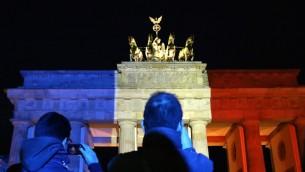 أشخاص يلتقطون صورا لبوابة براندنبورغ التي أُضيئت بألوان العلم العلم الفرنسي، 14 نوفمبر، 2015 في برلين، بعد يوم واحد من الهجمات الدامية التي وقعت في باريس. (AFP PHOTO / ISABELLE WIRTH)