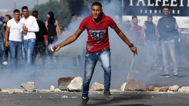 محتج فلسطيني يلقي قنبلة مسيلة للدموع ألقتها القوات الإسرائيلية خلال مواجهات مع جنود إسرائيليين عند حاجز حوارة، جنوبي مدينة نابلس بالضفة الغربية، 9 أكتوبر، 2015. (AFP PHOTO/JAAFAR ASHTIYEH)