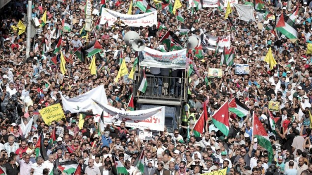 متظاهرون أردنيون يلوحون بالأعلام الأردنية والفلسطينية خلال مظاهرة بالقرب من السفارة الأردنية في العاصمة عمان تضامنا مع الفلسطينيي، 16 أكتوبر، 2015. (Khalil Mazraawi/AFP)