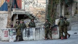 جنود إسرائيليون يقفون بالقرب من الموقع حيث حاول شاب فلسطيني طعن جندي قبل إطلاق النار عليه وقتله في مدينة الخليل بالضفة الغربية، 28 أكتوبر، 2015. (AFP Photo/Hazem Bader)