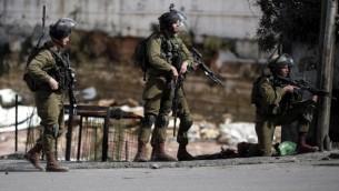 القوات الإسرائيلية تقف في شارع خلال مواجهات مع محتجين فلسطينيين في مدينة الخليل بالضفة الغربية، 30 أكتوبر، 2015. (AFP/Thomas Coex) (AFP/Thomas Coex)
