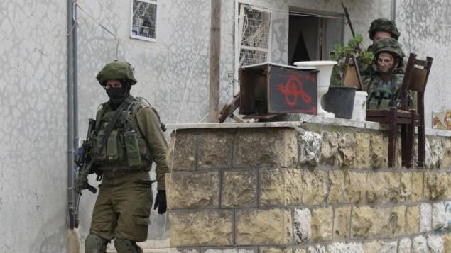 جنود اسرائيليين يفتشون منزلا فلسطينيا في الخليل، 7 نوفمبر 2015 (Hazem Bader/AFP)