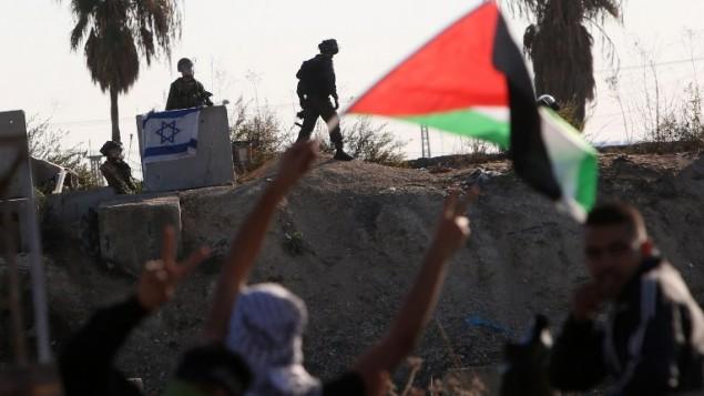 محتجون فلسطينيون يلوحون بالأعلام الفلسطينية خلال مواجهات مع القوات الإسرائيلية في مدينة طولكرم بالضفة الغربية، 12 نوفمبر، 2015. (Jaafar Ashtiyeh/AFP)