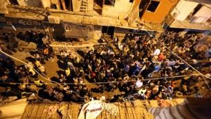 مواطنون وجنود يحتشدون في موقع تفجيرين إنتحاريين في منطقة برج البراجنة، في الضاحية الجنوبية للعاصمة اللبنانية بيروت، 12 نوفمبر، 2015. (AFP PHOTO / MARWAN TAHTAH)
