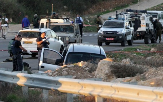 عناصر من الجيش والشرطة الإسرائيليين يقومون بتفتيش مركبة في أعقاب هجوم دام بالقرب من مستوطنة عوتنيئل، جنوبي مدينة الخليل بالضفة الغربية، 13 نوفمبر، 2015. (AFP/Hazem Bader)