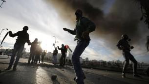 فلسطينيون يرشقون الحجارة باتجاه قوات الأمن الإسرائيلية خلال اشتباكات بالقرب من البيرة على ضواحي رام الله، 20 نوفمبر 2015 (AFP PHOTO/ABBAS MOMANI)
