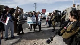 نشطاء سلام إسرائيليون وفلسطينيون يمرون أمام جنود إسرائيليين خلال تظاهرة في الضفة الغربية، 27 نوفمبر، 2015. (AFP PHOTO/THOMAS COEX)
